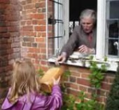 Image of a child passing a loaf to an elderly person through a window